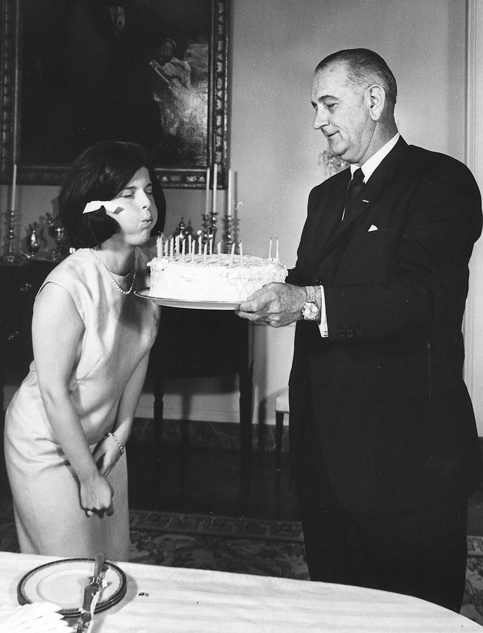 <p>President Lyndon B. Johnson holds a cake as his daughter Luci Baines blows out her birthday candles on her 17th birthday in July 1964.</p>