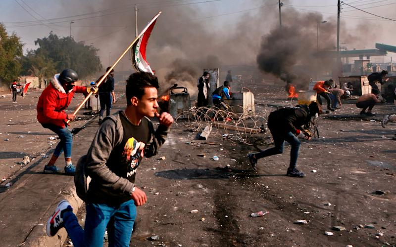 Anti-government protesters take cover while security forces use tear gas during clashes in central Baghdad, - AP