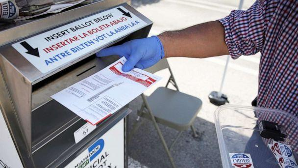 PHOTO: A poll worker casts a mail-in ballot for a voter at a drive-thru polling station during the primary election amid the COVID-19 outbreak in Miami, Aug. 18, 2020. (Marco Bello/Reuters, FILE)
