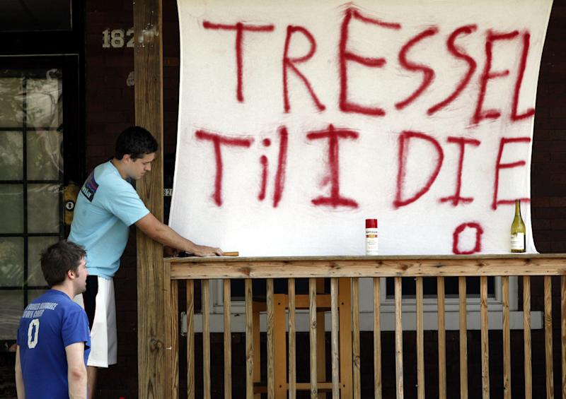 Ohio State students Curt Stine, left, and Matt Parker hang a sign on their porch near campus in support of former Ohio State football coach Jim Tressel, Monday, May 30, 2011, in Columbus, Ohio. Tressel, who guided Ohio State to its first national title in 34 years, resigned Monday amid NCAA violations from a tattoo-parlor scandal. (AP Photo/Terry Gilliam)