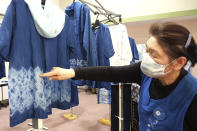 In this image from video, Kiyoko Mori, 65, the head of indigo dye group called Japan Blue, points out at one of displayed indigo dyed artwork at a community center where residents evacuated when the 2011 earthquake hit the area in Minamisoma, Fukushima Prefecture, northeastern Japan, on Feb. 20, 2021. After the Fukushima nuclear plant disaster a decade ago, nearby farmers weren't allowed to grow crops for two years because of radiation. After the restriction was lifted, two farmers in the town of Minamisoma found an unusual way to rebuild their lives and help their destroyed community. Kiyoko Mori and Yoshiko Ogura planted indigo and soon began dying fabric with dye produced from the plants. (AP Photo/Chisato Tanaka)