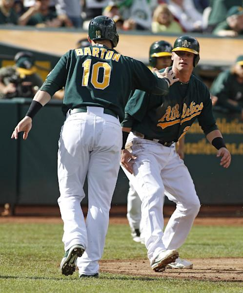 Oakland Athletics' Daric Barton (10) and Josh Donaldson shake hands after scoring on a Yoenis Cepedes single against the Minnesota Twins during the second inning of a baseball game, Saturday, Sept. 21, 2013, in Oakland, Calif. (AP Photo/George Nikitin)