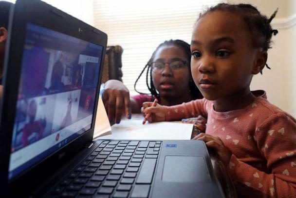 PHOTO: In this Feb. 10, 2021, file photo, Lear Preston, who attends Scott Joplin Elementary School, participates in her virtual classes as her mother, Brittany Preston, background, assists at their residence in Chicago. (Shafkat Anowar/AP, FILE)