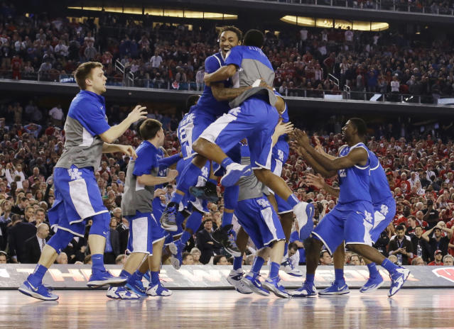 Kentucky celebrates after guard Aaron Harrison made a three-point basket in the final seconds against Wisconsin to win the game 74-73 during their NCAA Final Four tournament college basketball semifinal game Saturday, April 5, 2014, in Arlington, Texas. (AP Photo/David J. Phillip)