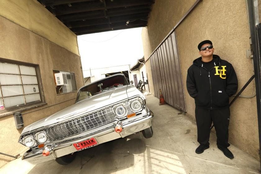 """LONG BEACH, CA - AUGUST 10, 2021 - Jonathan Rodriguez, 20, stands next to his 1963 Impala SuperSport lowrider at Speedy's Metal Finishing in Long Beach on August 10, 2021. Rodriguez did most of the updates to his car at the place owned by his father, Luis """"Speedy"""" Rodriguez. """"During quarantine I would spend a lot of time doing upgrades to the car,"""" said Jonathan. He added new batteries, added new coils, changed to one-way hydraulics and fixed the convertible top. Jonathan is a member of, """"High Class Car Club,"""" which was co-founded by his father. California's aftermarket industry, which is the largest in the nation flourished during the pandemic. It's made up of companies that help people modify their cars to help them go faster, run more efficiently, corner better, brake shorter and look better. These companies did record business in 2020 keeping up with owners like Rodriguez. (Genaro Molina / Los Angeles Times)"""