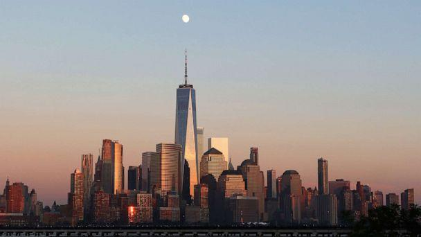 PHOTO: The moon rises as the sun sets on the skyline of lower Manhattan and One World Trade Center in New York City on July 31, 2020, as seen from Jersey City, New Jersey. (Gary Hershorn/Getty Images)