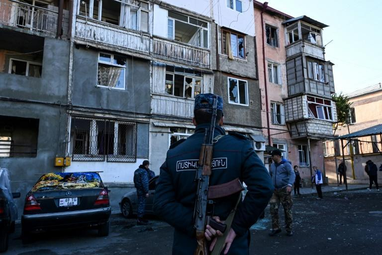 A police officer stands in front of an apartment building that was apparently damaged by recent shelling in the breakaway Nagorno-Karabakh region's main city of Stepanakert