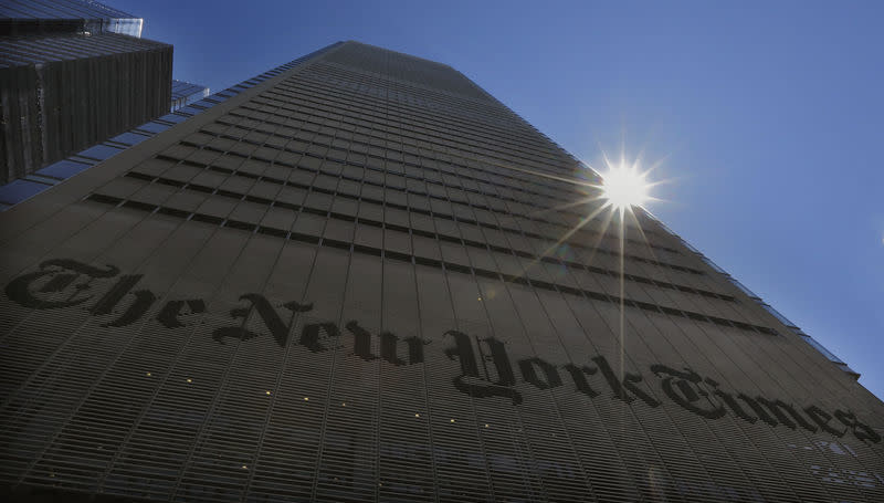 The sun peaks over the New York Times Building in New York