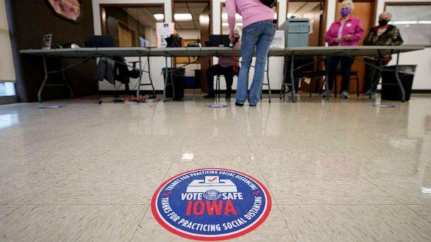 PHOTO: A local resident gets her ballot during early voting, Oct. 20, 2020, in Adel, Iowa. (Charlie Neibergall/AP)