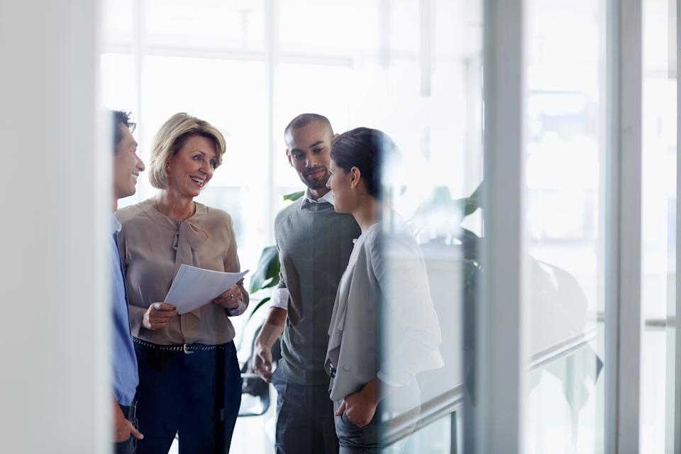 Smiling businesswoman discussing over document with colleagues in office
