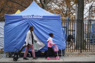 Pedestrians pass testing tent at a COVID-19 mobile testing site outside of a playground, Wednesday, Nov. 11, 2020, in the Brooklyn borough of New York. Restaurants, bars and gyms will have to close at 10 p.m. across New York state in the latest effort to curb the spread of the coronavirus, Gov. Andrew Cuomo announced Wednesday. Cuomo said the new restrictions, which go into effect Friday, are necessary because new coronavirus infections have been traced to those types of activities. (AP Photo/John Minchillo)