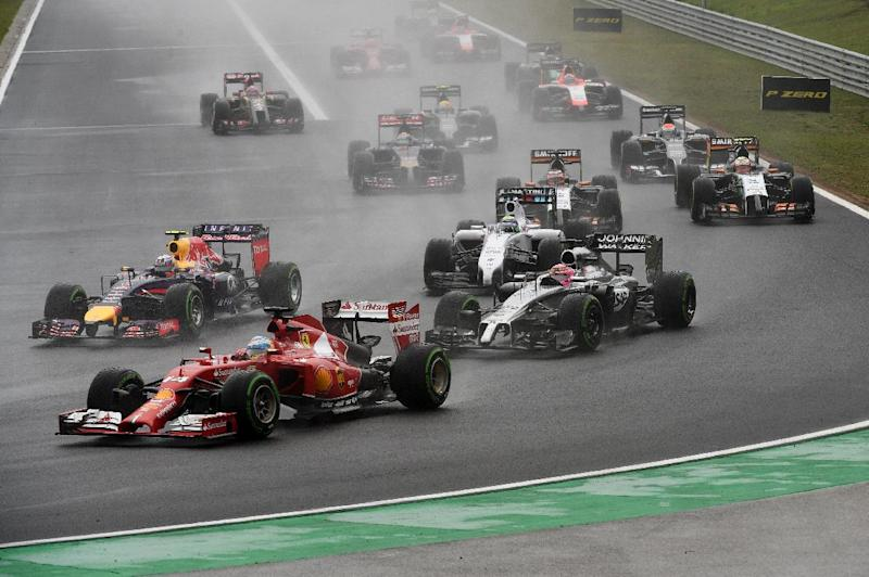 Fernando Alonso (front) drives through the rain ahead of Daniel Ricciardo after the start of the Hungarian Formula One Grand Prix at the Hungaroring circuit in Budapest on July 27, 2014