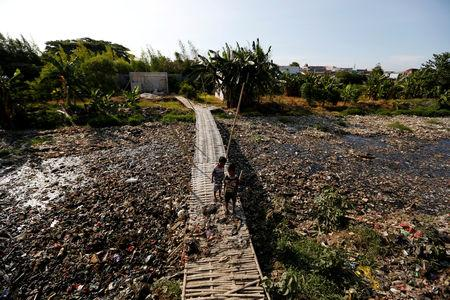 Children stand on a bridge near a river covered by rubbish in Bekasi, West Java province, Indonesia, January 7, 2019. REUTERS/Willy Kurniawan/Files