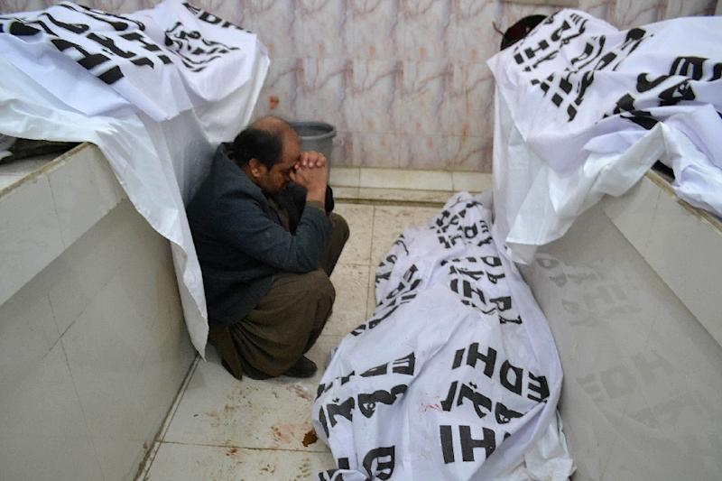A mourner grieves alongside bodies of blast victims at a hospital in Quetta, following a suicide attack near a polio vaccination centre, on January 13, 2016 (AFP Photo/Banaras Khan)
