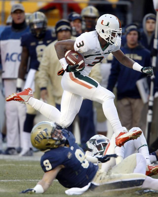 Miami wide receiver Stacy Coley (3) leaps past Pittsburgh defensive back Ray Vinopal (9) on his way to his second touchdown after making a catch in the first quarter of an NCAA college football game in Pittsburgh on Friday, Nov. 29, 2013. (AP Photo/Keith Srakocic)