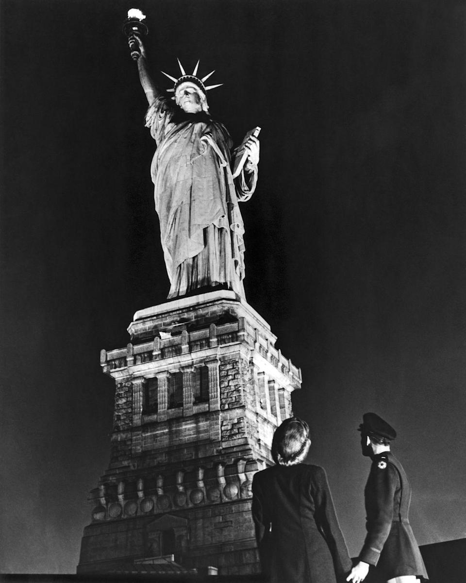 <p>A soldier and his companion steer away from V-E Day hoopla to gaze upon the Statue of Liberty. V-E Day marked the first time the Green Goddess was illuminated, except for a brief period on D-Day, since the Pearl Harbor attack.</p>