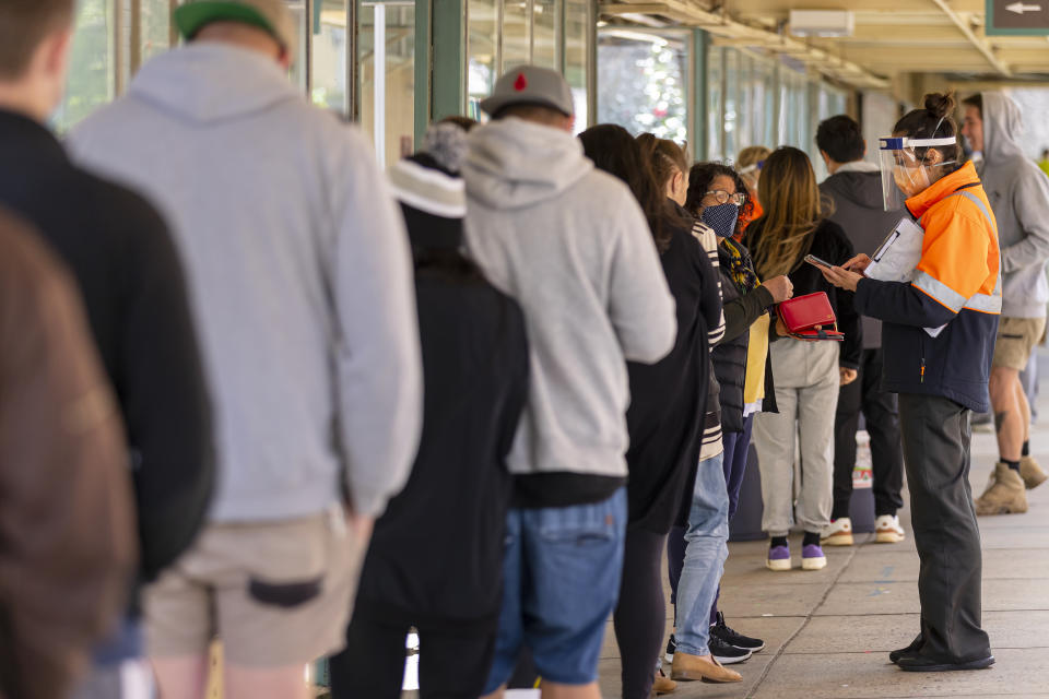 People check-in outside the Covid vaccination hub at the Heidelberg Repatriation Hospital in Melbourne, Monday. Source: AAP