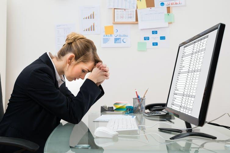 Woman at computer with spreadsheet on screen and head in hands.