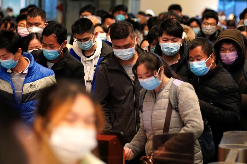 FILE PHOTO: Passengers wearing face masks arrive at a railway station in Wuhan