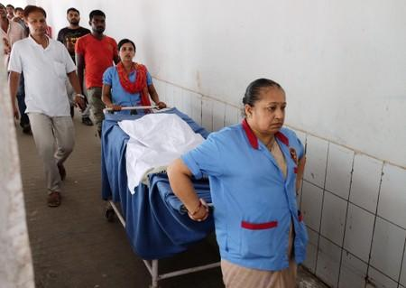 Staff carry the body of a girl who died of acute encephalitis syndrome to an ambulance at a hospital in Muzaffarpur