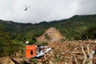 A helicopter flies over an area hit by a mudslide, caused by heavy rains brought by Storm Eta, as the search for victims continue in the buried village of Queja