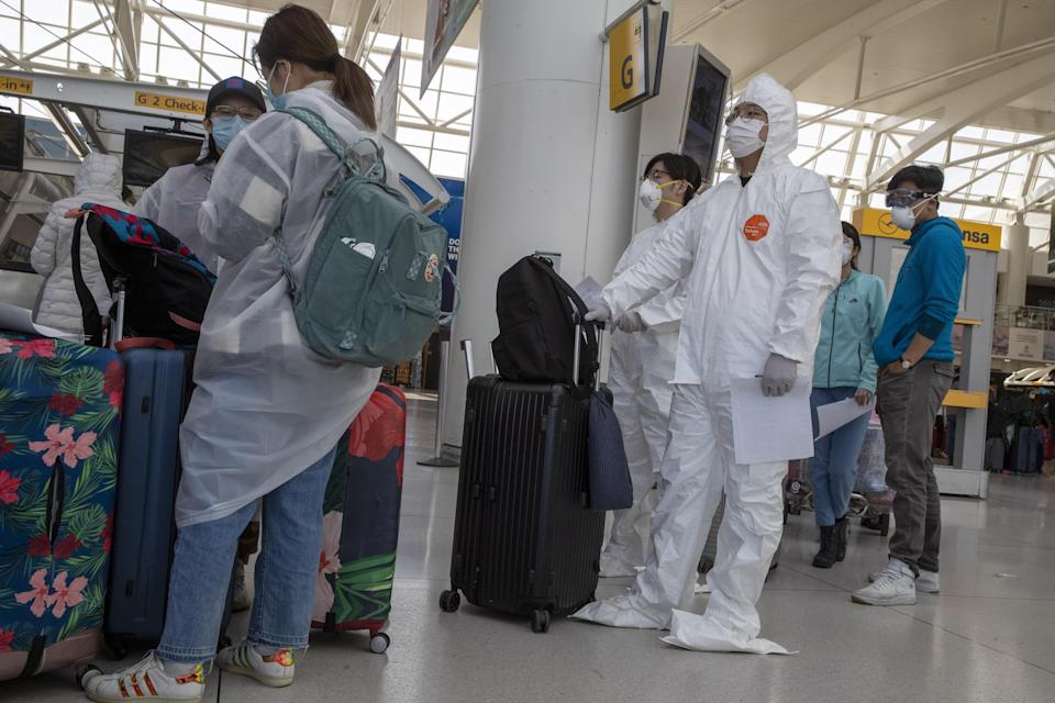 Passengers wear safety gear to fend off coronavirus as they wait in line to check in for their flights, Tuesday, March 24, 2020, at JFK airport in New York.