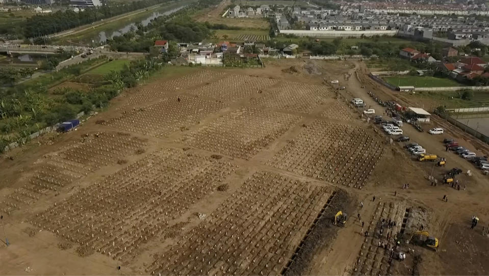 In this image from drone video, backhoes dig additional burial plots at the Rorotan cemetery, a graveyard built for COVID-19 victims in Jakarta, Indonesia on July 23, 2021. Indonesia surpassed the grim milestone of 100,000 official COVID-19 deaths on Wednesday, Aug. 4, 2021, as the country struggles with its worst pandemic year fueled by the delta variant, with growing concerns that the actual figure could be much higher with people also dying at home. (AP Photo/Andi Jatmiko)