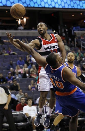Washington Wizards guard A.J. Price (12) loses control of the ball as he is fouled by New York Knicks forward Kurt Thomas (40) during the first quarter of an NBA preseason basketball game in Washington, Thursday, Oct. 11, 2012. (AP Photo/Ann Heisenfelt)