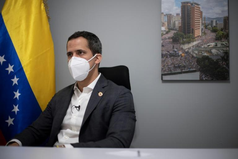 Venezuelan opposition leader Juan Guaido's home office features a national flag and a picture of a demonstration he led in 2019 -- protests that are increasingly rare in the country