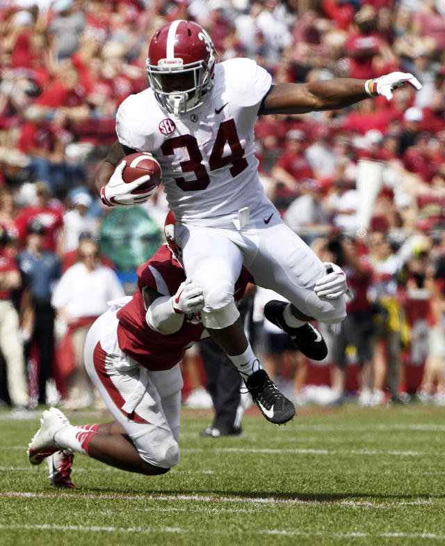 Alabama running back Damien Harris is tripped up by Arkansas defenders Kamren Curl in the second half of an NCAA college football game Saturday, Oct. 6, 2018, in Fayetteville, Ark. (AP Photo/Michael Woods)