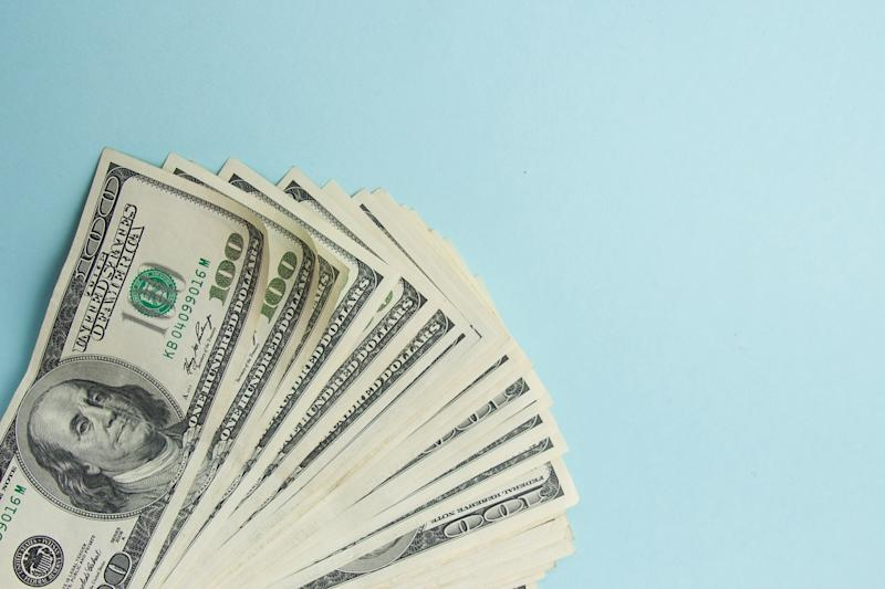 Stack of U.S. hundred dollar bills fanned out over a blue background.