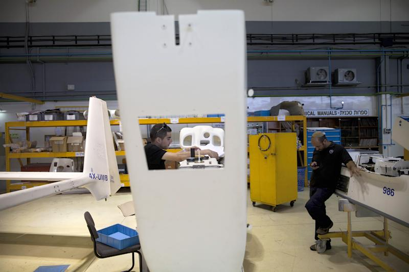 In this picture taken on Monday, May 28, 2013, Israel Aerospace Industries employees work on in a hangar, near Tel Aviv. In an expansive hangar in central Israel, workers toil on one of the world's most contentious aircraft, fitting dozens of drones with advanced sensors, cameras and lasers before they are shipped to militaries worldwide. Whereas drones are criticized elsewhere for being morally and legally objectionable, in Israel they are a source of pride. Israel has emerged as the world's leading exporter of the aircraft, putting it in a key position as the industry grows worldwide.(AP Photo/Oded Balilty)