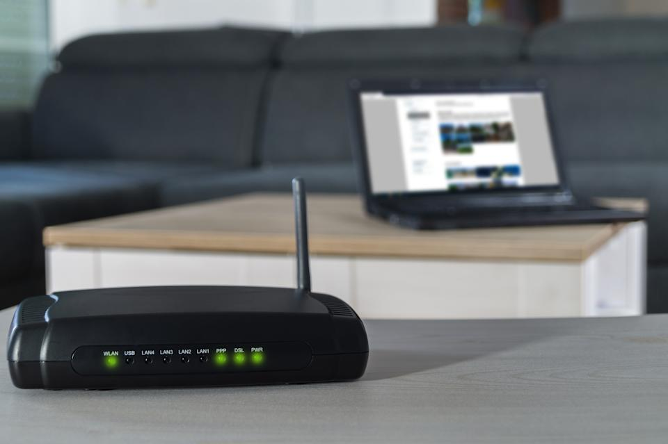Home internet connection. A wlan router on desk with notbook in background.
