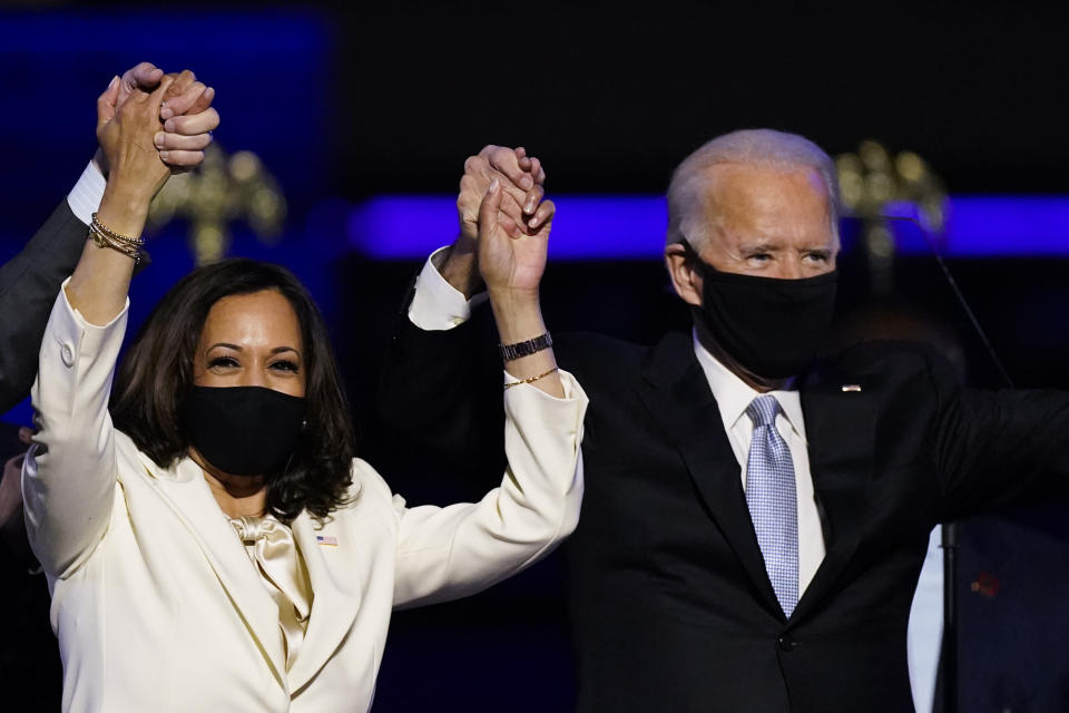 FILE - In this Nov. 7, 2020, file photo Vice President-elect Kamala Harris holds hands with President-elect Joe Biden and her husband Doug Emhoff as they celebrate in Wilmington, Del. Black policy leaders will play a pivotal role in President-elect Joe Biden's transition team, marking one of the most diverse presidential agency review teams in history. (AP Photo/Andrew Harnik, File)