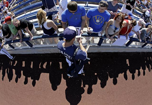 Milwaukee Brewers' Logan Schafer signs autographs before an exhibition spring training baseball game against the Chicago Cubs Monday, March 3, 2014, in Phoenix. (AP Photo/Morry Gash)