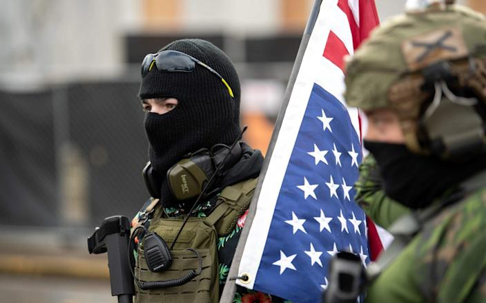 Members of the Boogaloo Boys stand armed in front of the Oregon Sate Capitol building in Salem - AFP