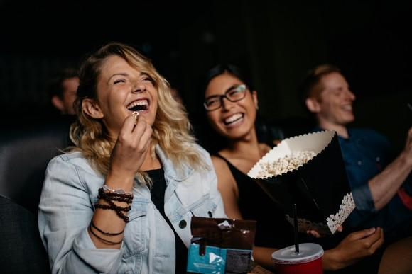 Friends laughing at a movie while eating popcorn