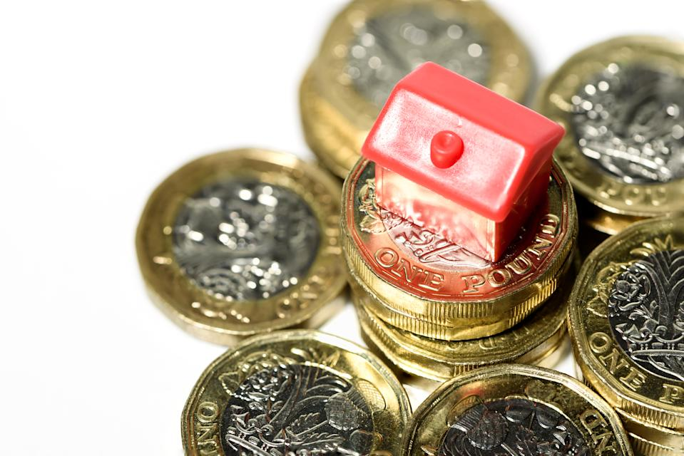 Macro close up of a Miniature house resting on new pound coins with a white background