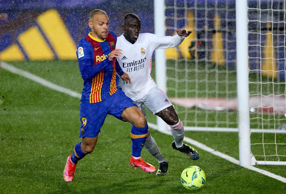 MADRID, SPAIN - APRIL 10: Martin Braithwaite of FC Barcelona is challenged by Ferland Mendy of Real Madrid during the La Liga Santander match between Real Madrid and FC Barcelona at Estadio Alfredo Di Stefano on April 10, 2021 in Madrid, Spain. Sporting stadiums around Spain remain under strict restrictions due to the Coronavirus Pandemic as Government social distancing laws prohibit fans inside venues resulting in games being played behind closed doors. (Photo by Angel Martinez/Getty Images)
