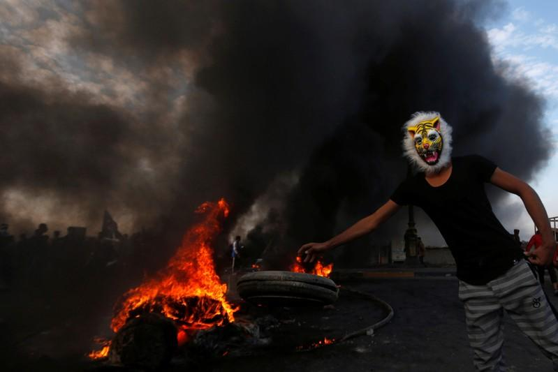 A masked protester throws a tire into fire during ongoing anti-government protests in Basra