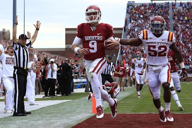 Oklahoma quarterback Trevor Knight (9) runs in for a touchdown in front of Iowa State's Jeremiah George (52) in the third quarter of an NCAA college football game in Norman, Okla. on Saturday, Nov. 16, 2013. (AP Photo/Alonzo Adams)