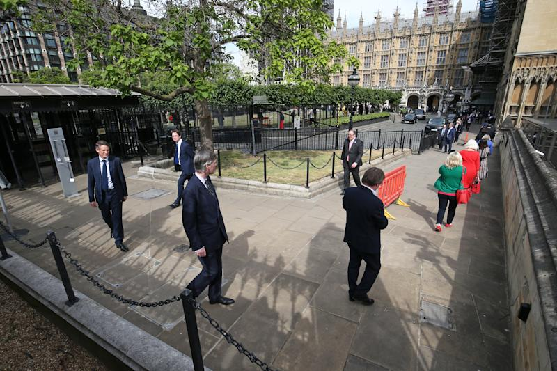Members of Parliament, including Leader of the House of Commons Jacob Rees-Mogg, queue outside the Houses of Commons in Westminster, London, as they wait to vote on the future of proceedings, amid a row over how Commons business can take place safely.