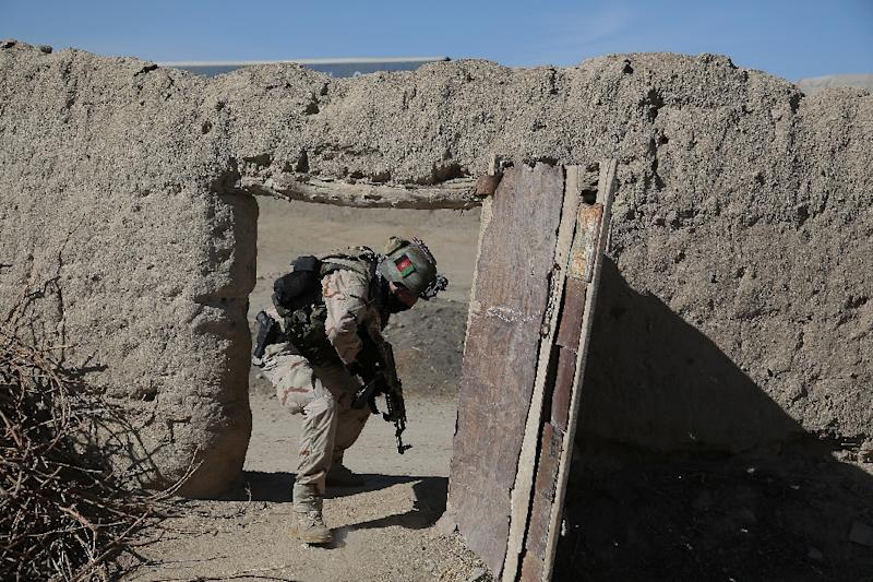 An Afghan policeman enters a courtyard during an anti-Taliban operation in the Andar district of Ghazni province, on February 4, 2015 (AFP Photo/Rahmatullah Alizadah)