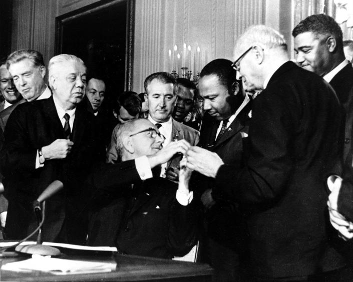 <p>U.S. President Lyndon B. Johnson reaches to shake hands with Dr. Martin Luther King Jr. after presenting the civil rights leader with one of the 72 pens used to sign the Civil Rights Act of 1964 in Washington, D.C., on July 2, 1964. Surrounding the president, from left, are, Rep. Roland Libonati, D-Ill., Rep. Peter Rodino, D-N.J., Rev. King, Emanuel Celler, D-N.Y., and behind Celler is Whitney Young, executive director of the National Urban League. (AP Photo) </p>