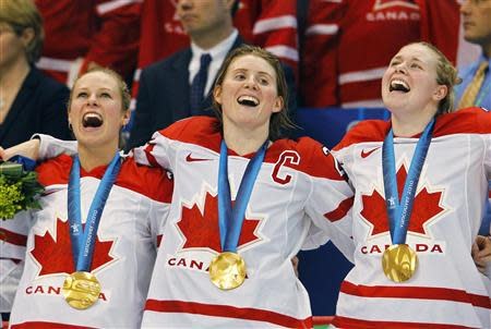 Canada's Bonhomme, captain Wickenheiser and Irwin celebrate their gold medal victory over the U.S. in their women's ice hockey game at the Vancouver 2010 Winter Olympics in this file photo