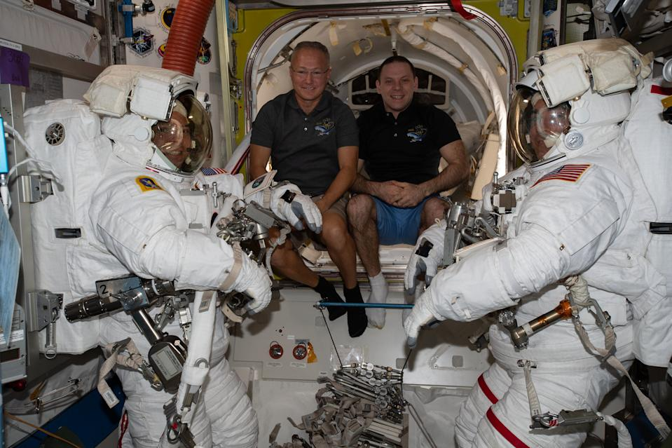 In this image, Expedition 63 flight engineers NASA astronaut Doug Hurley (middle left) and cosmonaut Ivan Vagner (middle right) helped to prepare NASA astronauts Bob Behnken and Chris Cassidy for a spacewalk on June 26, 2020. Cassidy and Behnken stepped out for a spacewalk in which they replaced aging nickel-hydrogen batteries on the space station with brand new lithium-ion batteries. The pair embarked on another battery swap spacewalk today (July 1.)