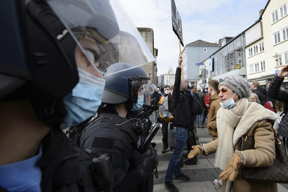 "A woman speaks to police officers on duty at a rally under the motto ""Free citizens Kassel - basic rights and democracy"" in Kassel, Germany, Saturday, March 20, 2021. According to police, several thousand people were on the move in the city center and disregarded the instructions of the authorities during the unregistered demonstration against Corona measures. (Swen Pfoertner/dpa via AP)"