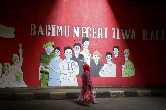 "A woman walks past a coronavirus-themed mural honoring health and other essential workers, in Jakarta, Indonesia, Wednesday, Aug. 26, 2020. Writings on the mural read: ""Our body and soul for the country."" (AP Photo/Dita Alangkara)"