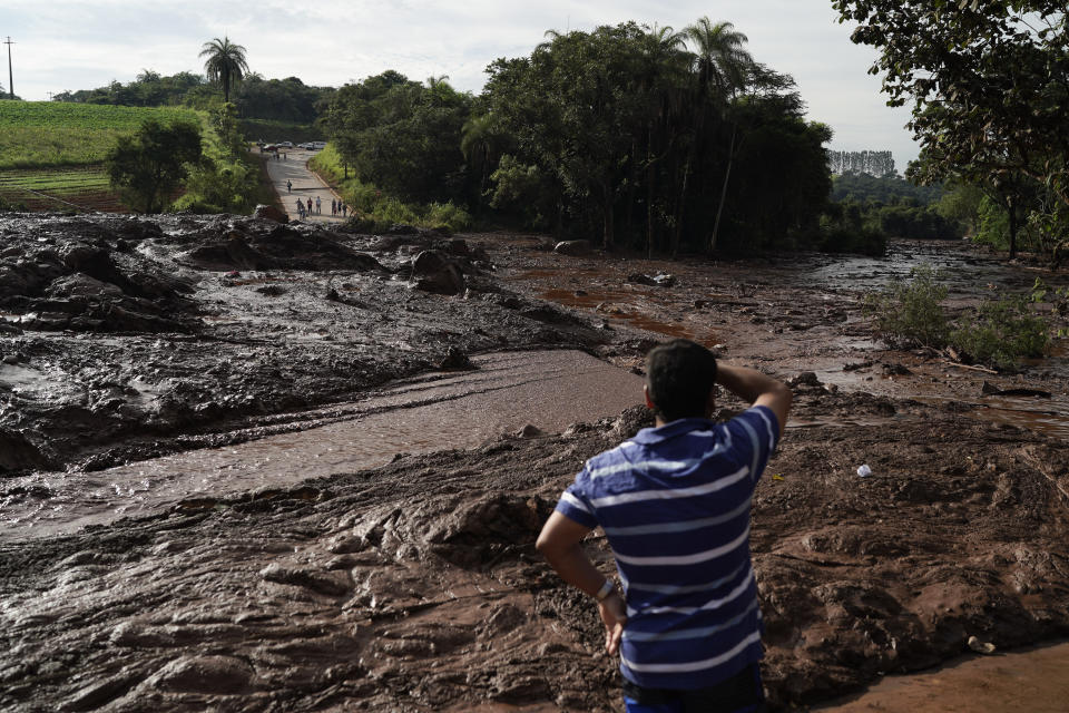 A man stands at a blocked road after a dam collapsed near Brumadinho, Brazil, Saturday, Jan. 26, 2019. The dam that held back mining waste collapsed, inundating a nearby community in reddish-brown sludge, killing at least seven people and leaving scores of others missing. (AP Photo/Leo Correa)