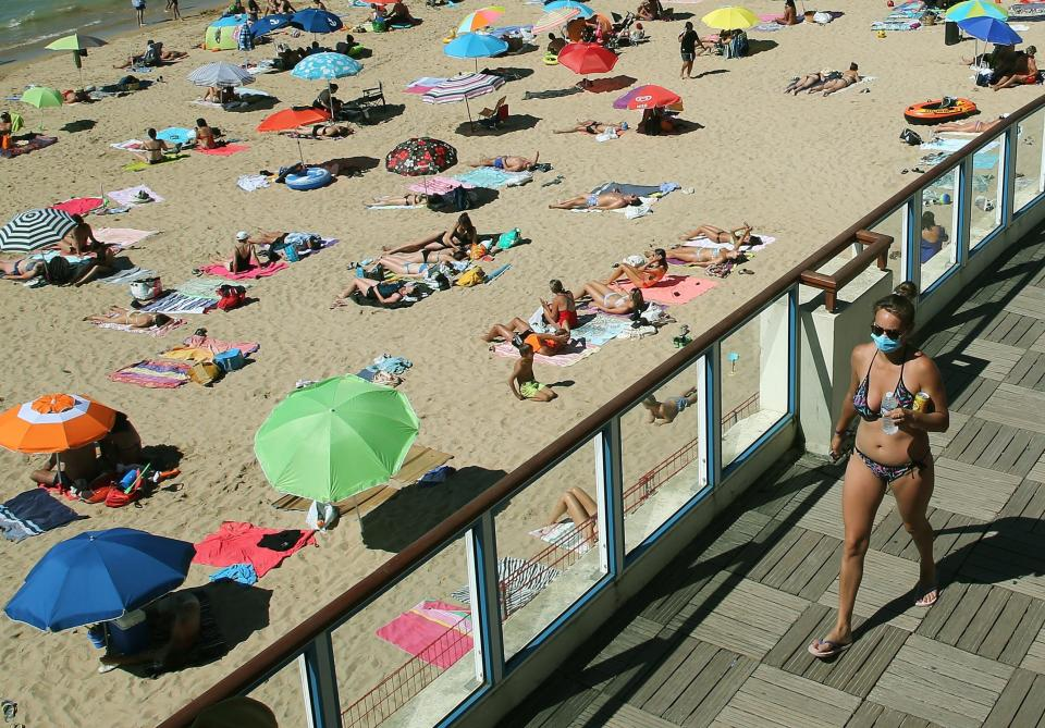 FILE - In this Wednesday, Aug. 5, 2020 file photo woman walks, wearing a face mask to protect against coronavirus, near the beach, in Saint Jean de Luz, southwestern France. Since Monday, 69 towns in western France imposed outdoor mask rules to slow the spread of coronavirus. Britain will require all people arriving from France to isolate for 14 days - an announcement that throws the plans of tens of thousands of holiday makers into chaos. The government said late Thursday Aug. 13, 2020 that France is being removed from the list of nations exempted from quarantine requirements because of a rising number of coronavirus infections. (AP Photo/Bob Edme, File)